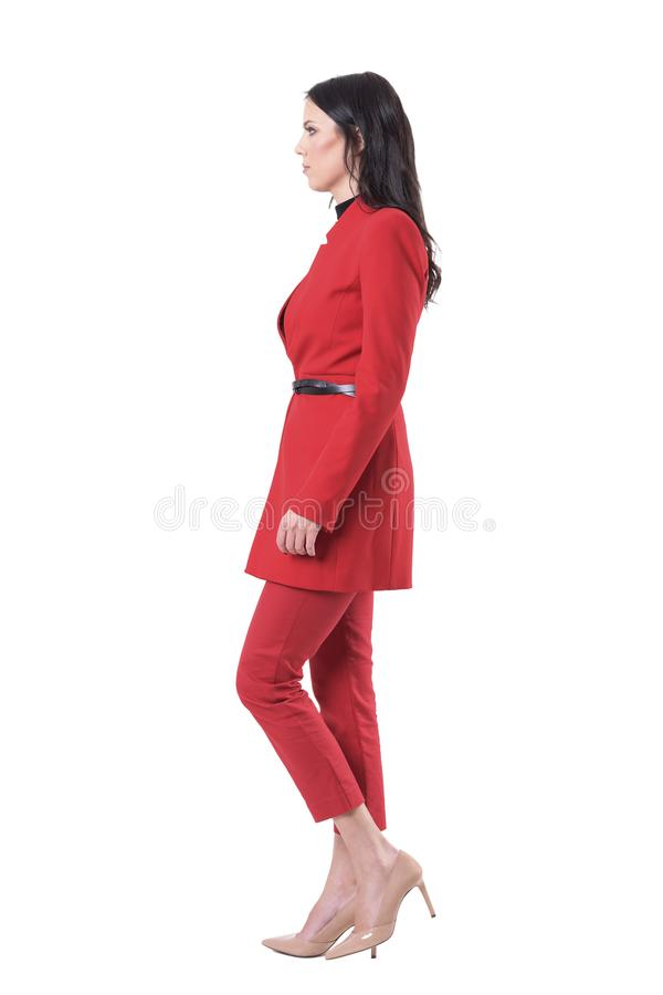 Side view of confident serious business woman in red suit walking and looking ahead. royalty free stock photos