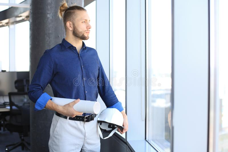 Side view of confident young man holding blueprint and hardhat and looking away while standing indoors royalty free stock photography