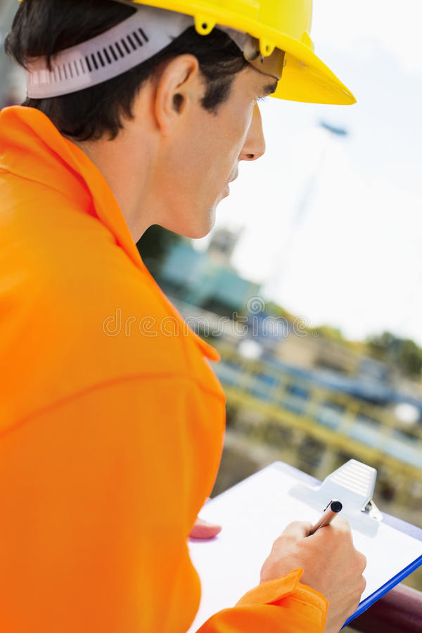 Side view of construction worker writing on clipboard at construction site royalty free stock images