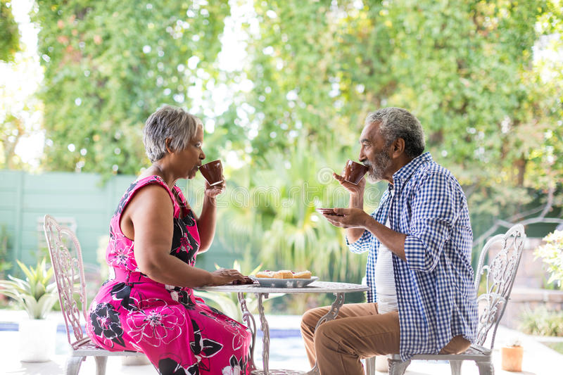 Side view of couple drinking coffee in yard royalty free stock image