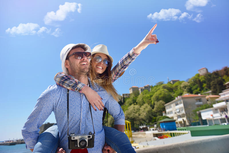 Side view of a couple of 2 tourists with a suitcase sitting relaxing and enjoying vacations in a colorful promenade. royalty free stock photography