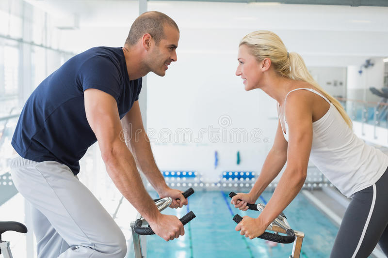 Side view of couple working on exercise bikes at gym royalty free stock photos