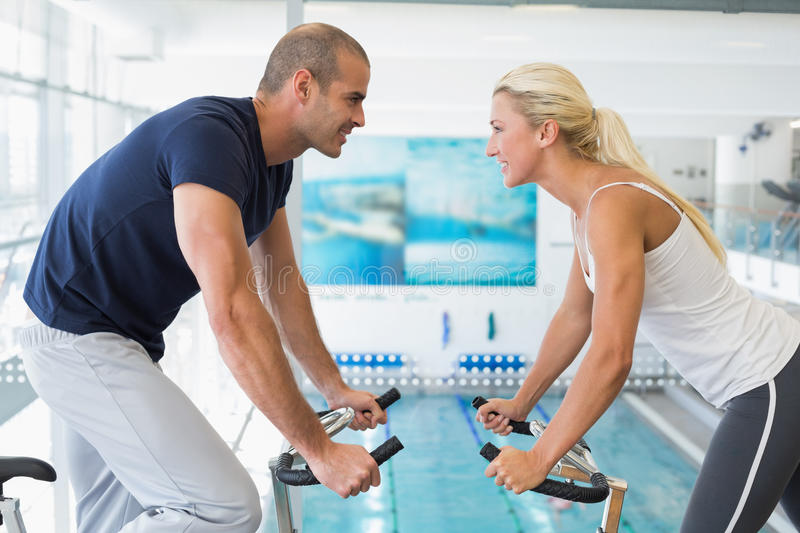 Side view of couple working on exercise bikes at gym stock image