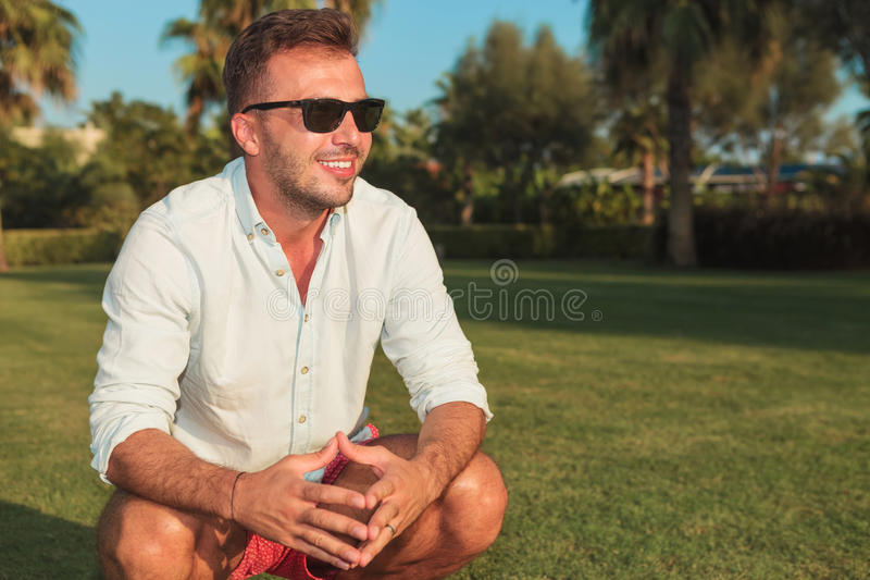 Side view of a crouched smiling man wearing sunglasses royalty free stock image