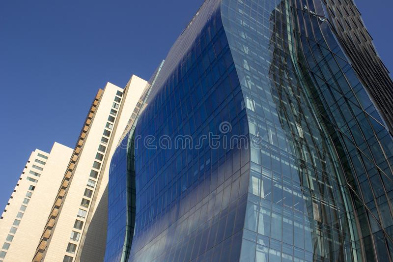 Side view of a curved blue glass window wall of a modern and elegant corporative building, next to a yellowish classical one. stock images
