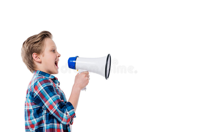 Side view of cute little boy holding megaphone and screaming. Isolated on white royalty free stock photo