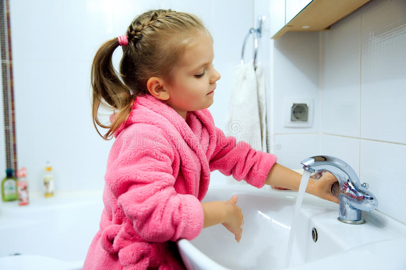 Side view of cute little girl with ponytail in pink bathrobe washing her hands. stock image