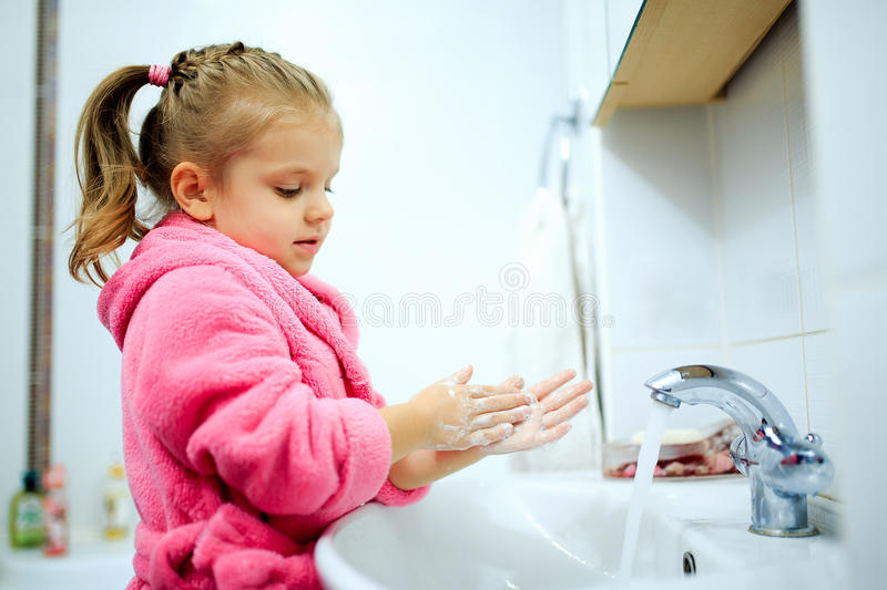 Side view of cute little girl with ponytail in pink bathrobe washing her hands. Copyspace stock photography