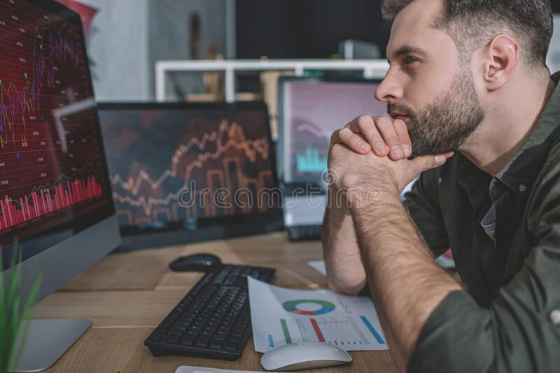 Side view of data analyst developing protection for computer systems with computer. In office stock image