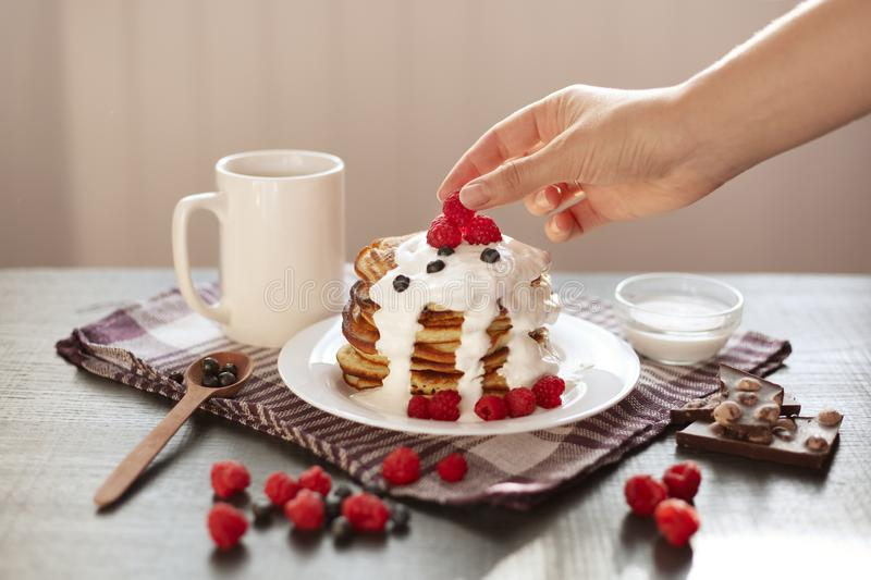 Side view of delicious pancakes with fresh berries and sour cream, baker putting raspberrry on top of muffins stack, tasty stock photo