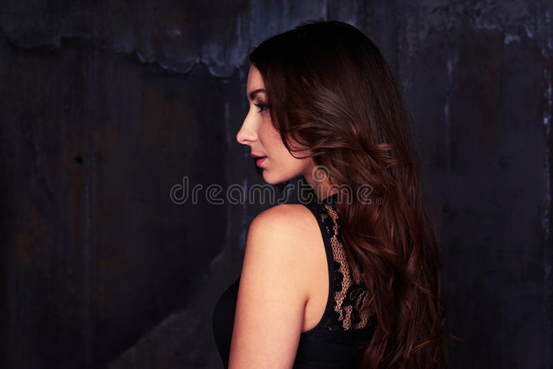 Side view of delightful female wearing lace black dress looking royalty free stock photos