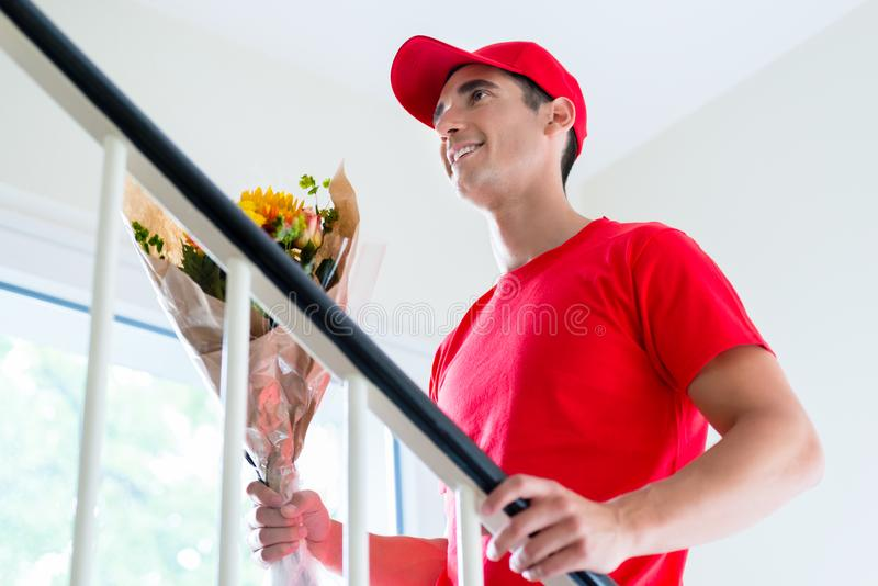 Delivery man holding flower bouquet gift royalty free stock photos