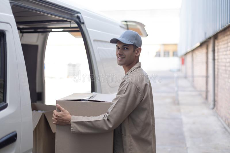 Delivery man carrying cardboard boxes outside the warehouse. Side view of delivery man carrying cardboard boxes outside the warehouse. This is a freight royalty free stock photo