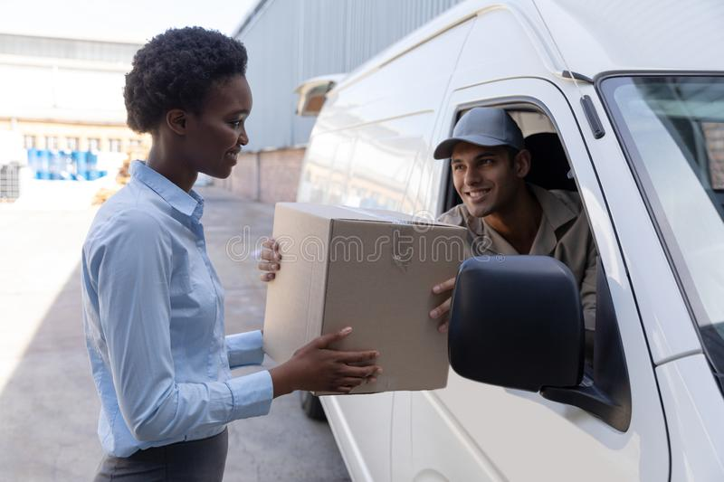 Delivery man giving parcel to warehouse manager outside the warehouse stock image