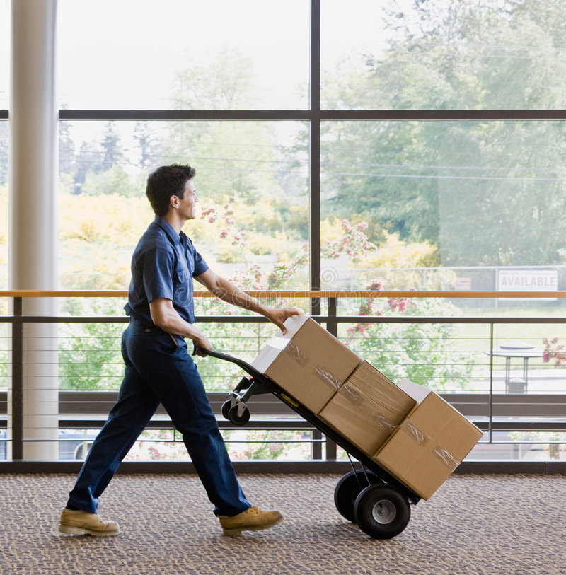 Side view of delivery man ipushing stack of boxes stock image