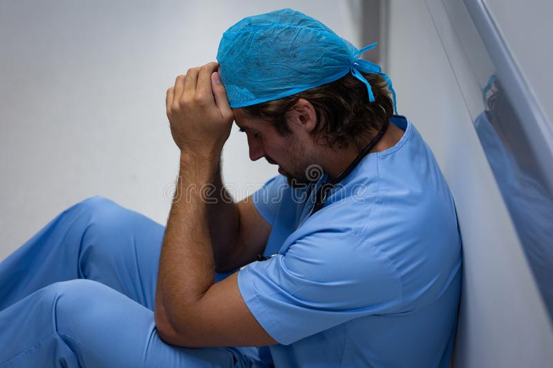 Depressed male surgeon sitting and leaning in the corridor at hospital stock photo