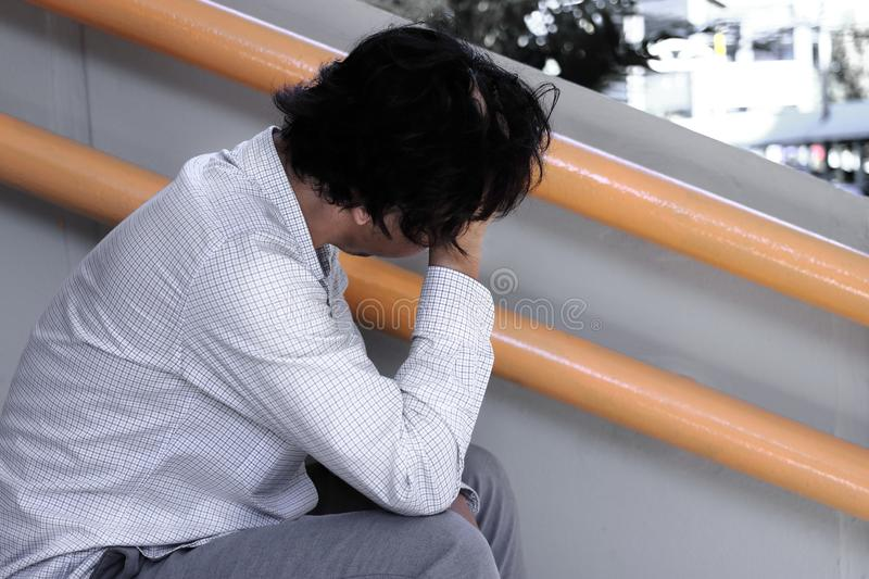 Side view of depressed stressed young Asian business man with hands touching head and feeling disappointed or exhausted with job. royalty free stock image