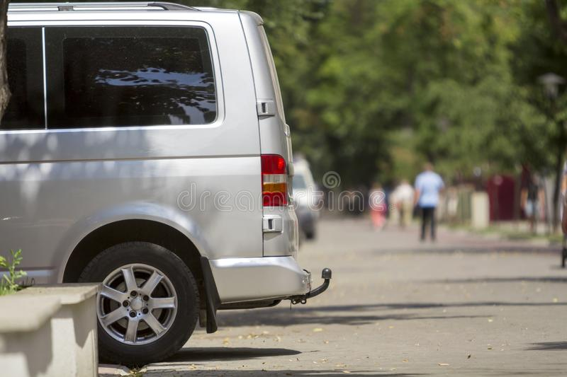 Side view detail of white passenger medium size luxury minibus v. An parked on summer city street pavement with blurred silhouettes of pedestrians on green stock photography
