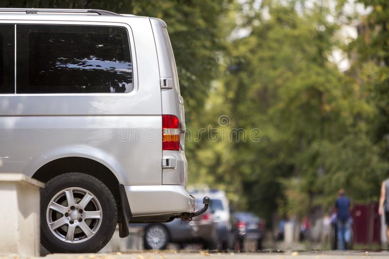 Side view detail of white passenger medium size luxury minibus van parked on summer city street pavement with blurred silhouettes royalty free stock image