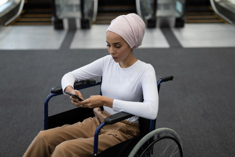 Young disabled mixed-race female executive using mobile phone in the lobby royalty free stock photo
