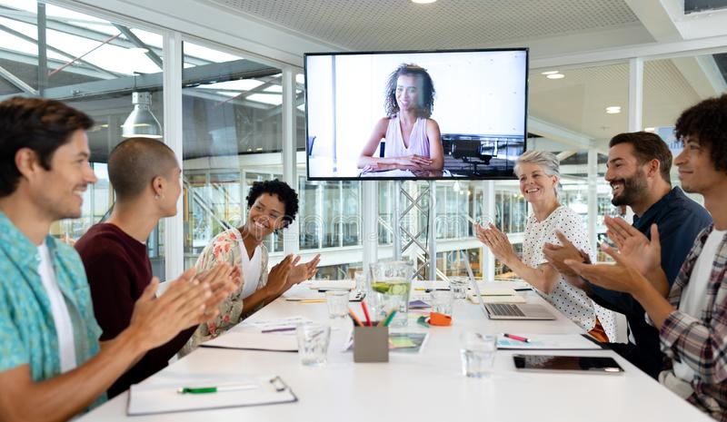 Business people attending video conference at conference room in a modern office. Side view of diverse business people attending video conference at conference stock photo