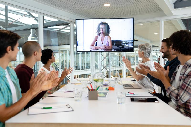 Business people attending video conference at conference room in a modern office. Side view of diverse business people attending video conference at conference royalty free stock photos