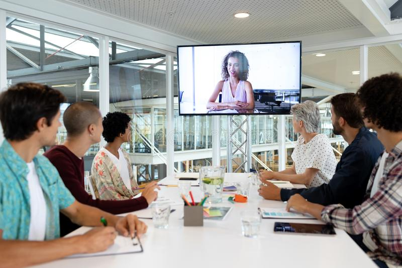 Business people attending video conference at conference room in a modern office. Side view of diverse business people attending video conference at conference royalty free stock photo
