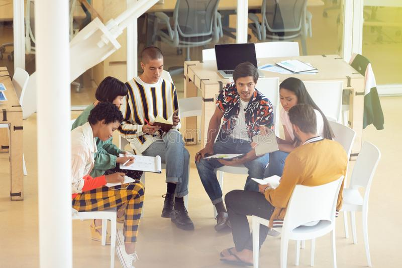 Business people sitting together and having group discussion in office. Side view of diverse Business people sitting together and having group discussion in stock photos
