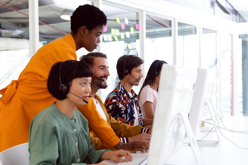 Customer service executive trainer assisting her team at desk. Side view of diverse customer service executive trainer assisting her team at desk in office stock images