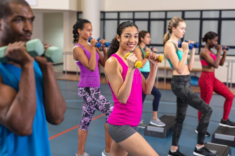 Fit people exercising with dumbbells on aerobic stepper. Side view of diverse fit people exercising with dumbbells on aerobic stepper in fitness center. Bright royalty free stock photos