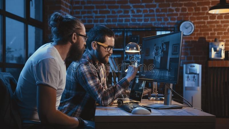 Men creating cartoon on computer stock images