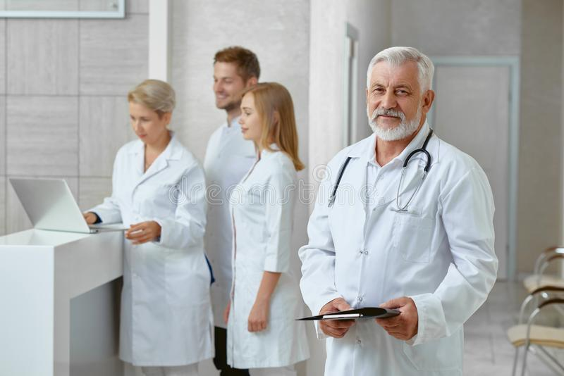 Side view of doctor and his coleagues in clinic. royalty free stock photography