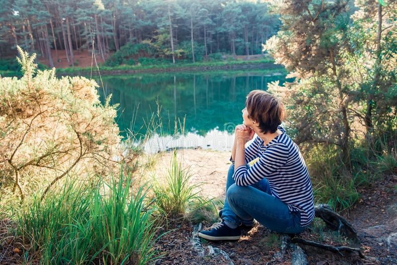 Side view dreamy woman sitting on the lakeside and enjoying beautiful serene day looking at lake and forest. Idyllic calm peaceful royalty free stock photography