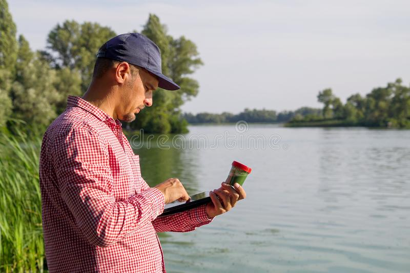 Side view of ecologist on river bank entering data on green algae on tablet. Research of ecological problems. environment, nature, save earth royalty free stock images