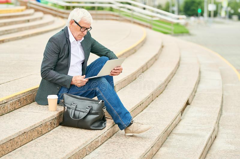 Aged businessman using laptop on stairs royalty free stock image