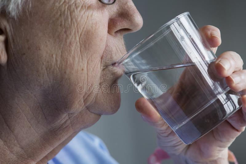 Side view of elderly woman drinking water stock photography