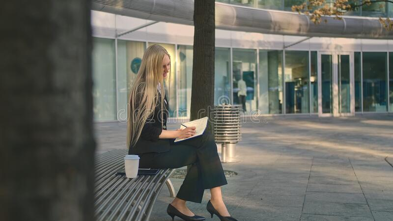 Successful young woman taking notes outdoors. Side view of elegant businesswoman sitting on bench in patio and writing royalty free stock photo