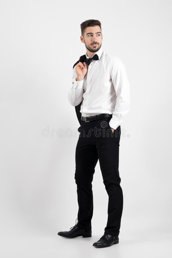 Side view of elegant man holding suit jacket over his shoulder looking away with hands in pockets royalty free stock images