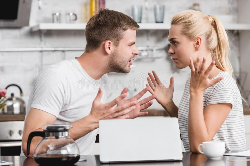Side view of emotional young couple arguing and looking at each other in kitchen relationship difficulties. Concept royalty free stock image