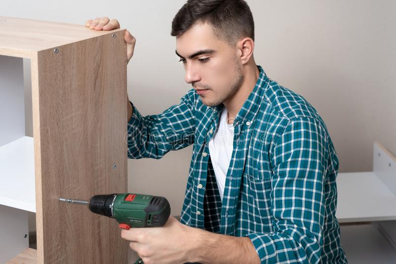 Side view of European man in shirt with electric screwdriver in hand engaged in the Assembly of furniture royalty free stock photography