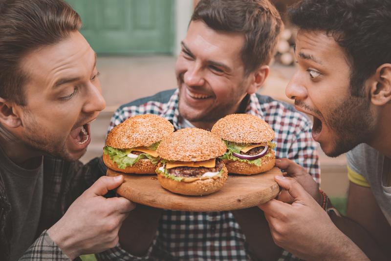 Side view of excited young men biting fresh. Tasty hamburgers royalty free stock images