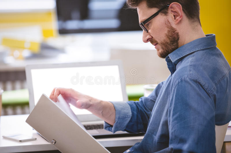 Side view of executive reading documents at office royalty free stock photography