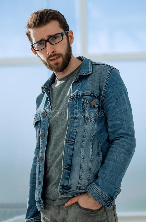 Side view.fashionable young man in a denim jacket stock images