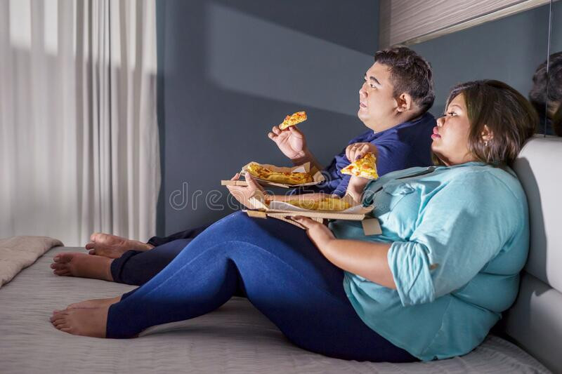 Side view of fat Asian couple eating pizza royalty free stock photos