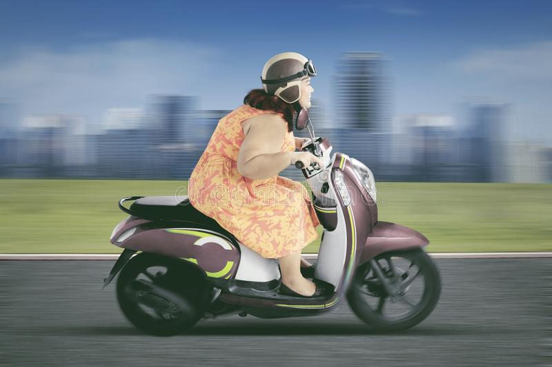 Fat woman driving a motorcycle on the highway royalty free stock photography
