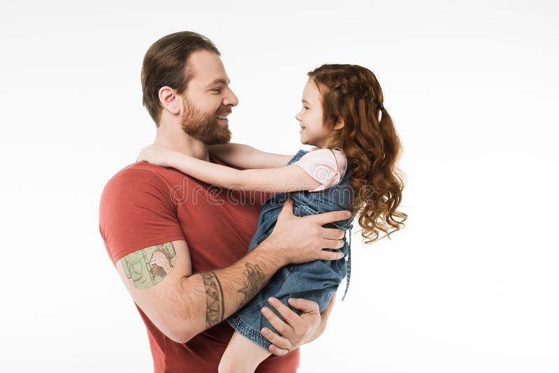 Side view of father holding little daugther in hands stock photo