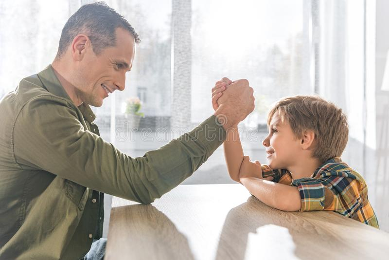 side view of father and little son arm wrestling together stock image