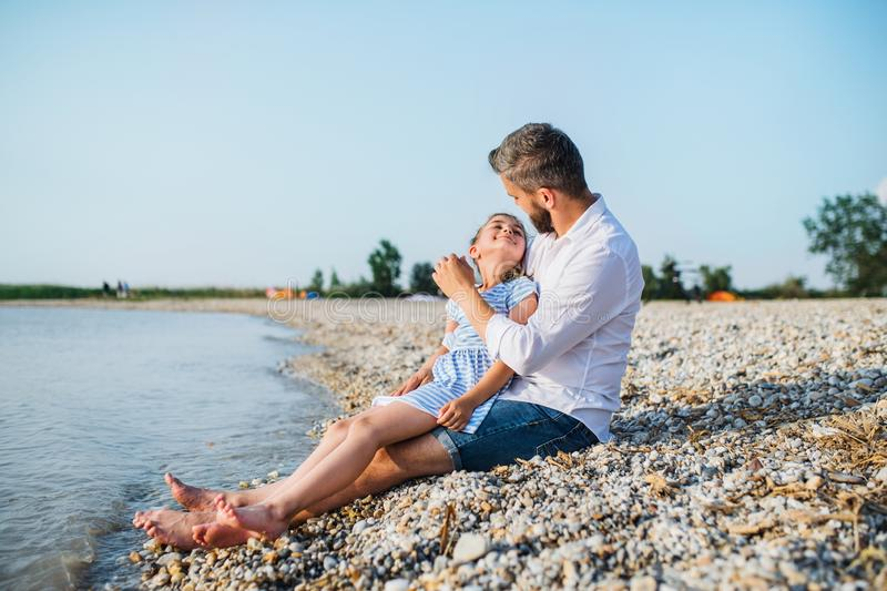 Side view of father and small daughter on a holiday sitting by the lake. royalty free stock photos