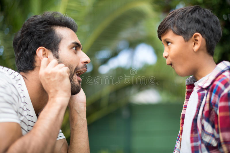 Side view of father and son making faces while playing stock images