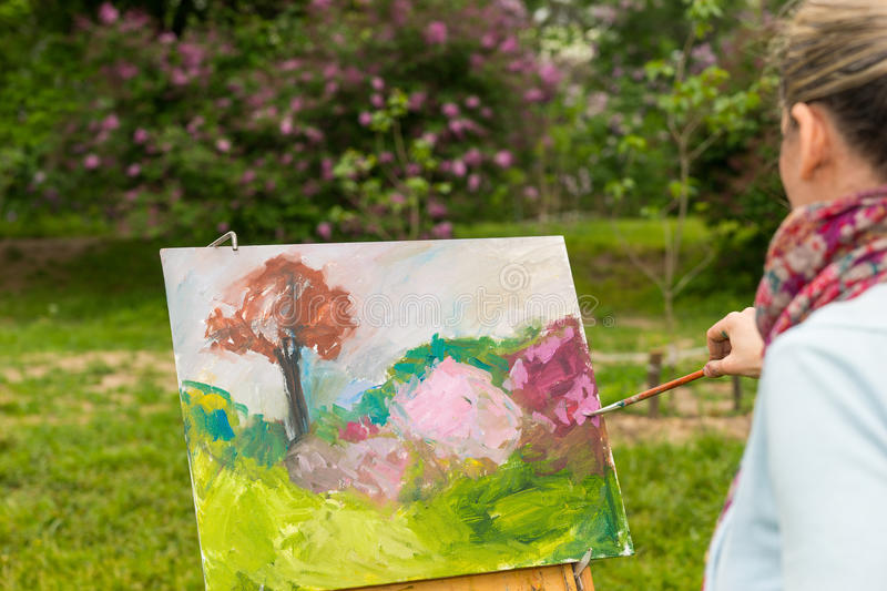Side view of a female artist painting royalty free stock photography